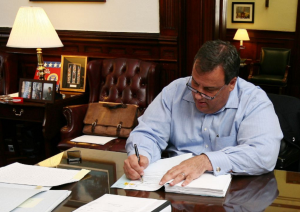 Christie at desk signing budget