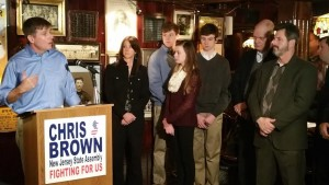 Brown (podium), surrounded by family and supporters, formally launches his reelection campaign.