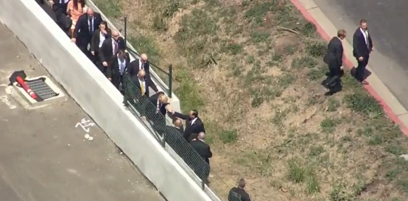 Trump crossing a border-like fence to circumvent protesters and reach the California GOP convention in Burlingame, south of San Francisco, on 4/29/16